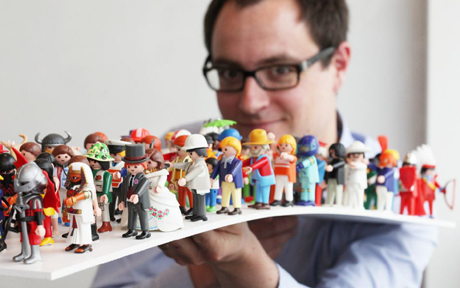 May0022971. The Daily Telegraph. Reporter Harry Wallop holds a tray of Playmobil figures from 1974 to the present, in the Playmobil Headquarters in Nuremberg, Germany. Playmobil is a toy manufacturer, which began making small plastic figures in 1974 and has since turned them into an iconic and internationally-recognisable toy, enjoyed by millions of children. Wednesday May 19, 2010.